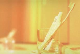 コップに立て掛けてある歯ブラシと歯磨き粉